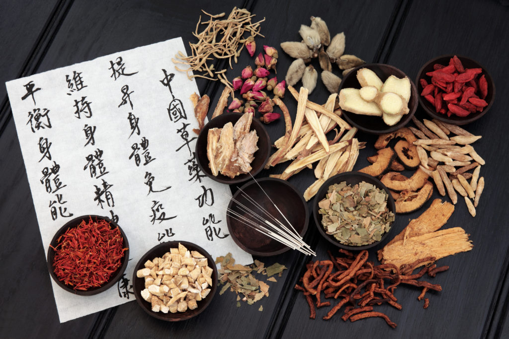 Acupuncture needles with chinese herbal medicine selection and mandarin calligraphy script on rice paper describing the medicinal functions to maintain body and spirit health and balance body energy.